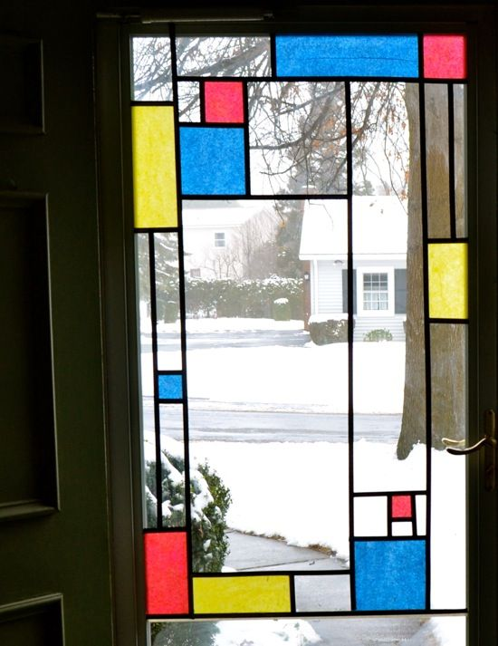Window art that resembles the work of Piet Mondrian. It uses tissue paper on glass, and the outline is black Acid-Free Masking Tape.