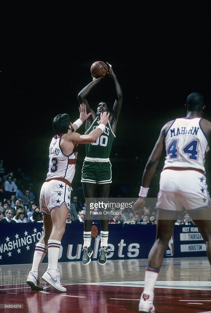BALTIMORE, MD - CIRCA 1980's: Robert Parish #00 of the Boston Celtics shooting a jump shot over Jeff Ruland #43 of the Washington Bullets during a mid circa 1980's NBA basketball game at the Baltimore Coliseum in Baltimore, Maryland. Parish played for the Celtics from 1980-94.