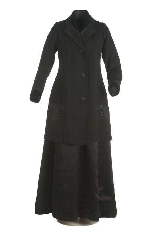 Traje sastre   ca. 1909  La chaqueta, larga y en lana de color negro con cuello vuelto y solapas en terciopelo liso y lana. Se cierra en el delantero con botones y va decorada con una aplicación de algodón y botones que recuerdan ornamentaciones militares. La falda, en raso de seda en color negro, es recta en el delantero y fruncida en el centro de la espalda.  MT099878-79