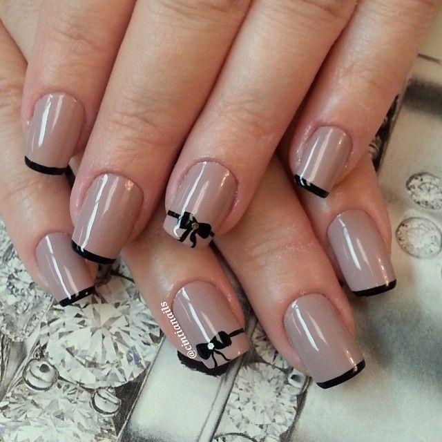 Tan nail polish; black tips; bow