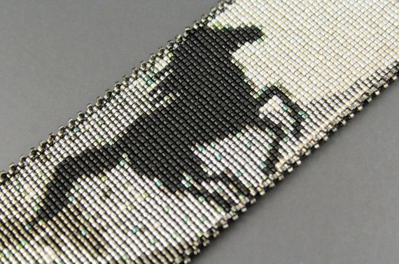 Ce bracelet/manchette extra large a été faite par moi sur un métier à tisser. Un seul cheval noir mat alimente charcoal ligné argent et étain avec éclaboussures de Sarcelles vers la nuance plus légère de létain de lustre opaque. Les bords sont bordées de ma frange « post and rail » cassé. Le brassard est fixé avec deux citations de boucle et talon. Très Western !   * Matériel : Graines de Miyuki Delica perles Perles (taille 11), Swarovski double cône (8mm), fil Nymo D * Technique : Loomw...