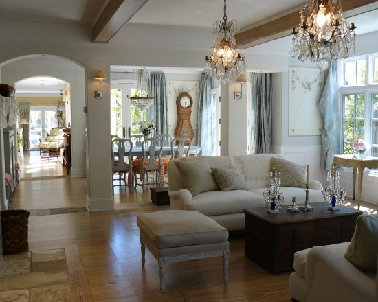 Beamed ceiling neutral wood floors and white upholstery living room area opens into the dining