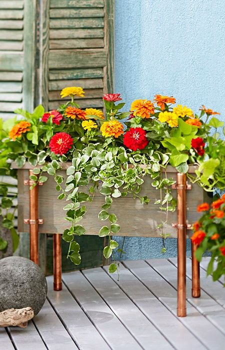 A DIY cedar planter box with cool copper accents hides plant containers and elevates your floral arrangement.