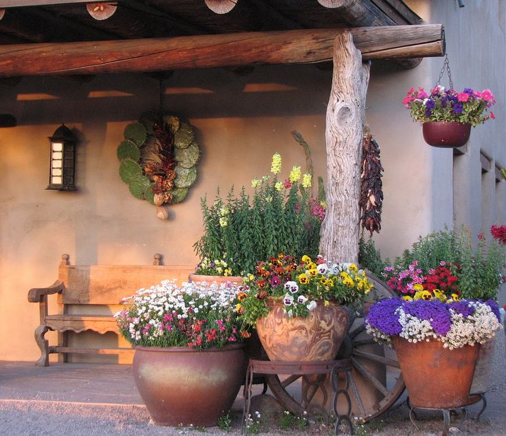 https://flic.kr/p/6KNRJK | The front porch | Isn't this a great spot to sip on some coffee and watch the sun set? This is so typical SW....old Mexican style bench, vigas, wreath made from cactus pads, adobe, wagon wheel, planter made from horse shoes, clay pots. You have it all here.  The photo was taken at a horse ranch.