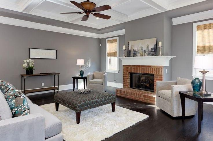 déco salon gris blanc bois : peinture grise, cheminée en brique rouge, tapis blanc et table basse en bois