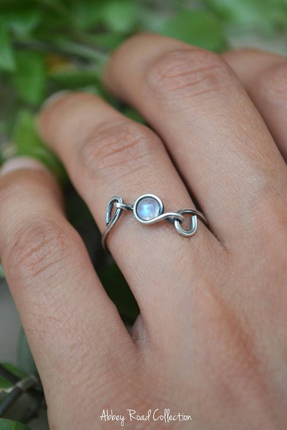 Moonstone Silver Wire Wrapped Ring This unique wire wrapped ring contains a lovely Rainbow Moonstone encased in sterling silver filled wire. This dainty ring can be worn by itself or together as a stacking ring with your other favorites! The moonstone is separately attached to #SterlingSilverWire