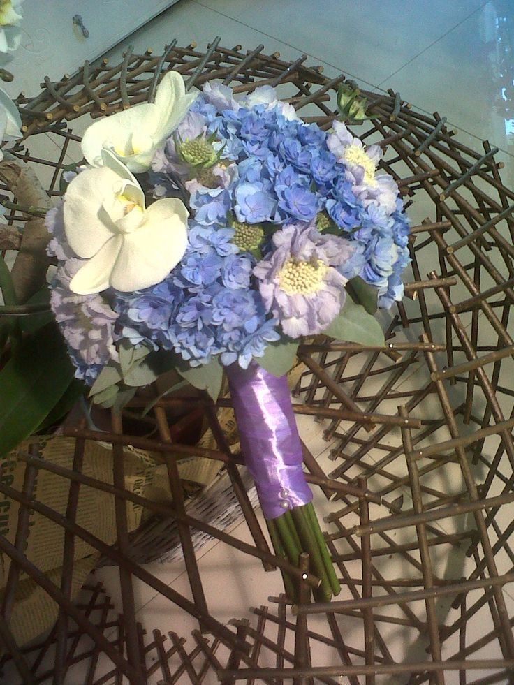 Bridal bouquet made with blue hydrangea,white phalaenopsis orchid and scabiosa