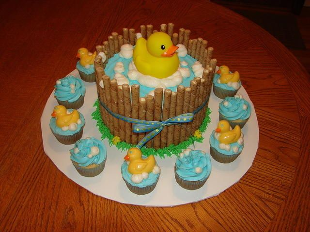 """8"""" 2-layer round cake surrounded by pirouettes with a rubber duck on top. Cupcakes surround with chocolate ducks for decor"""