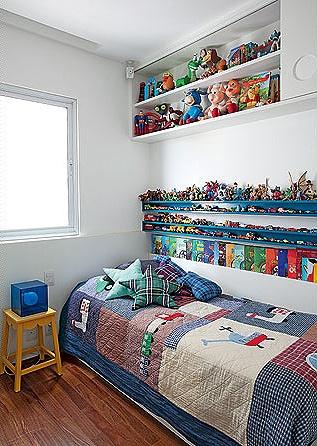 O quarto tem nichos de madeira, onde ficam os carrinhos e os livros. Para aproveitar o espaço em cima da cama foi feito o armário com portas de correr. Projeto da arquiteta Claudia Pecego