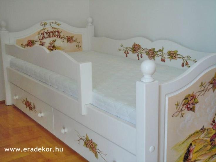 Az ágyikó a szobában, teljes pompájában - Anna névreszóló tömörfenyő indásvirágos-manós mintával festett fehér gyerekágy. Fotó azonosító: AGYANN03