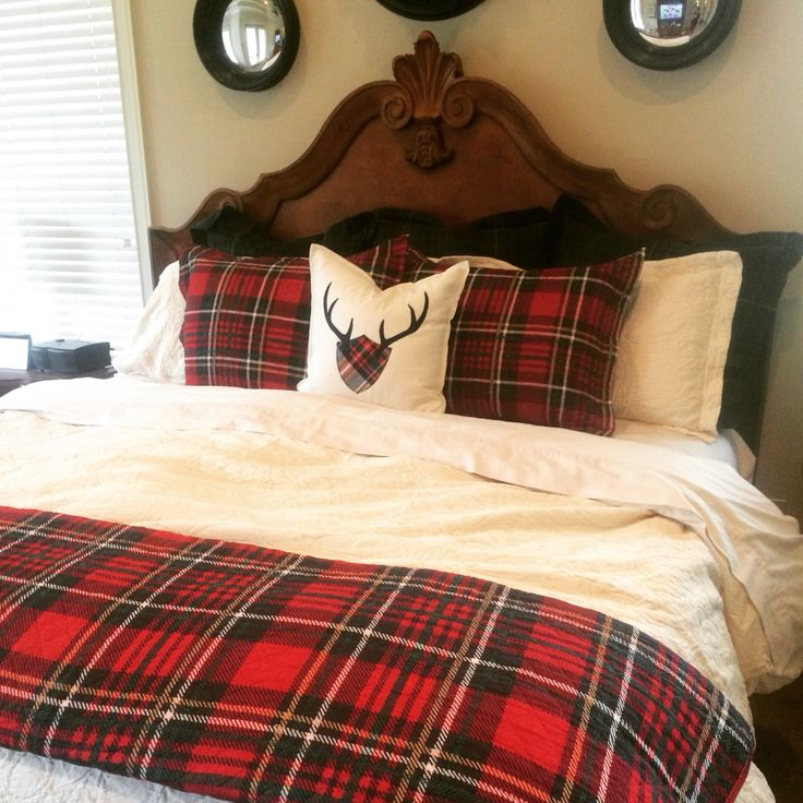 Christmas bed with red tartan, navy plaid and cream matelasse. Bedding by Ralph Lauren and Pottery Barn. Antler plow from Etsy. Bed by Century Furniture. Design by Evans Construction and Design.