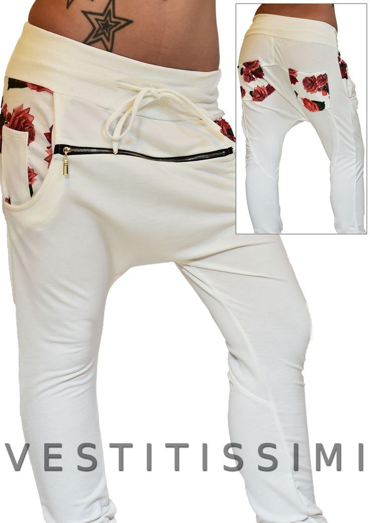 Pantalone donna sportivo colore bianco con stampa floreale, cerniera frontale orizzontale, fascia elastica e laccio in vita. Pantaloni fitness tuta stile harem con cavallo basso.
