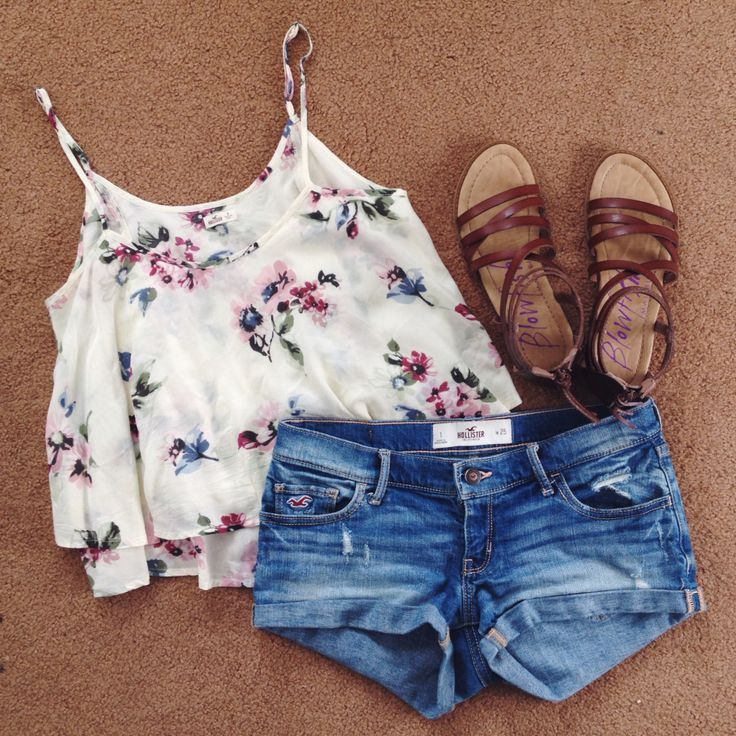 White noodle strap crop top with floral on it with some plain jean shorts and sandels More