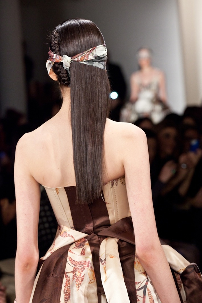 A blindfolded model walks down the Alexandre Herchcovitch Fall/Winter 2013 runway. Hair guru Rolando Beauchamp created the unique half down, half braided hairstyle.