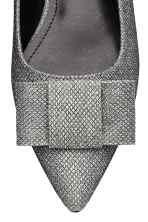 Sapatos rasos com laço: Sapatos rasos em pele sintética brilhante com biqueira fina e laço à frente. Forro e palmilhas em pele sintética. Solas de borracha.