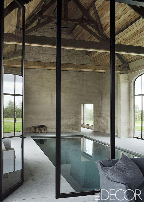 Esta poolhouse en el campo belga era un antiguo granero, y cuenta con vigas originales de acero. La piscina está revestida con azulejos de mosaico de vidrio, el entorno está revestido con piedra azul belga.