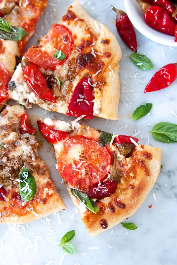 A homemade pizza recipe made easy with our DeLallo Italian Pizza Dough Kit, featuring zesty crumbled Italian sausage, Calabrian chili peppers, creamy sweet mascarpone, slices of Roma tomatoes and fresh basil.
