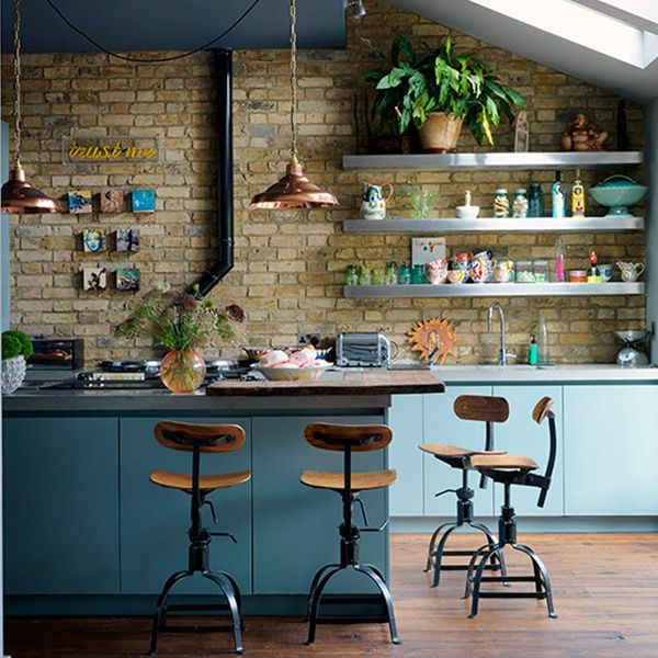 Cool blue base cabinets with exposed brick and open shelving above. Vintage wood counter stools and copper pendant add soul. It may just be the light, but the blue cabinets seem to be different tones of blue, creating an awesome ombre effect. Very earthy kitchen, with colors plucked straight from nature.: