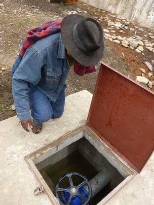 El proyecto ha capacitado y organizado los agricultores de Rumi Corral para que puedan gestionar y administrar la presa y el sistema de riego sin necesidad de apoyo externo. En la foto, un miembro del comité de riego utiliza la válvula principal del sistema de riego, en la base de la presa.