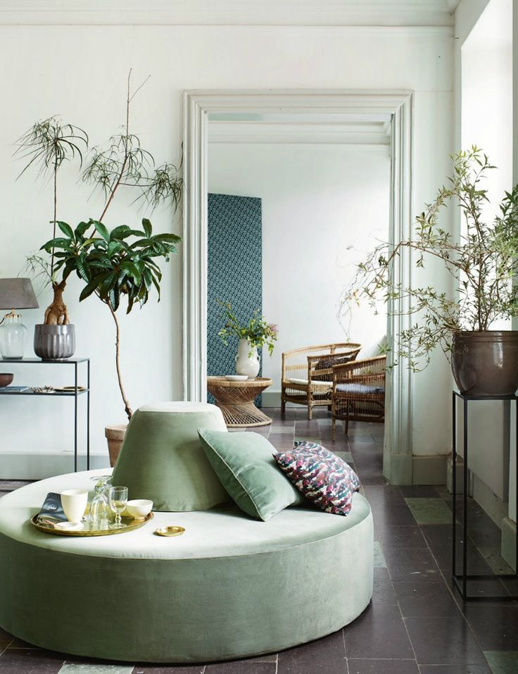 Calm and bright living room with a round velvet couch and lot's of green hints.