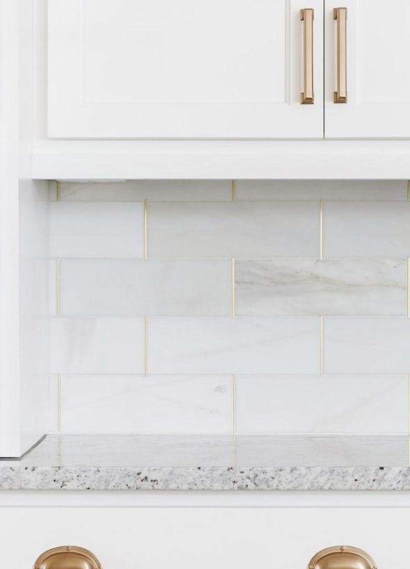 Kitchen backsplash is honed marble by the Tile Shop with brass schluter strips.