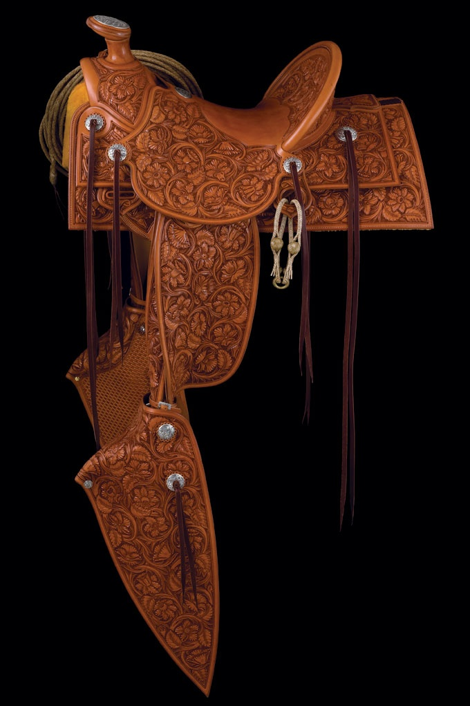 Dale Harwood 2008 Gear ~ TCAA - This is a complete outfit a large property owner might have owned in the late 1800s or early 1900s. The A fork saddle with square skirts has full flower stamping, full double stirrup leathers and 26-inch tapaderos. It includes a bridle with spade bit, romal reins and under bridle bosal and a horse hair neck rope. Other accessories are rawhide reata and hobbles as shown on saddle. The bit and the saddle silver were fabricated and engraved by Dale Harwood.