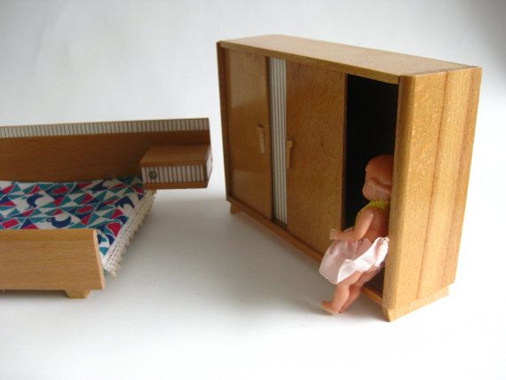 Dollhouse furniture from the 60s. Bed, Wardrobe/linencloset, dressing table and stool made of wood. All in good vintage condition. Only the mirror shows some minor scratches. The furniture comes with the doll. The doll has a mark in the back of the neck. It is a diamond shape with text in it but what it says I can not read. Under the mark says Made in Italy. The sizes of the wardrobe/linencloset is about 4 ½ inches high and 6 ¼ inches wide. The bed with the bedsides is 9 inc...
