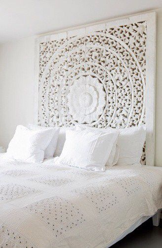 Moroccan carved timber bedhead in white room
