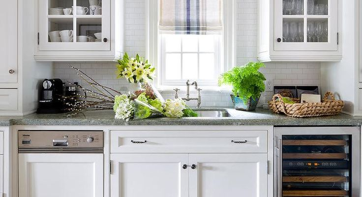 Cottage kitchen boasts a a stainless steel sink and hook and spout faucet placed…