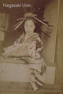 花魁とは主に江戸で用いられた遊女の別称。もとは上級遊女にのみ用いられたが、後には女郎一般をいうようになった。この写真は前者。衣裳は、紗綾、縮緬、羽二重、羅紗、ビロード、金襴緞子、綸子などぜいたくの限りを尽くし、髪には前後6本ずつのかんざし、2本の櫛のほかに長い笄をさした。