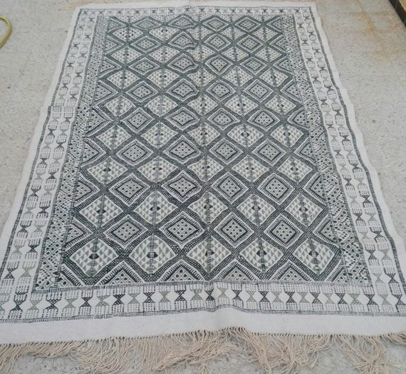 "Fabrication: Hand Made Type: mergoum Composition: 100% Wool Dimensions: 252 x 152 cm .  99,2*59,8 inches Origin: Tunisia  The Mergoum is a woven floor rug embroidered on a layer of cotton which gives it a rigid and solid look. The Mergoum is typically made in the towns of Oudhref, El Jem, and Karioun in Tunisia using ancient weaving techniques. Our Mergoum are handmade in the town of Kairoun. The origin of Mergoum is Berber. The diamond shapes that dominate the Mergoum rug are called ""regma""…"