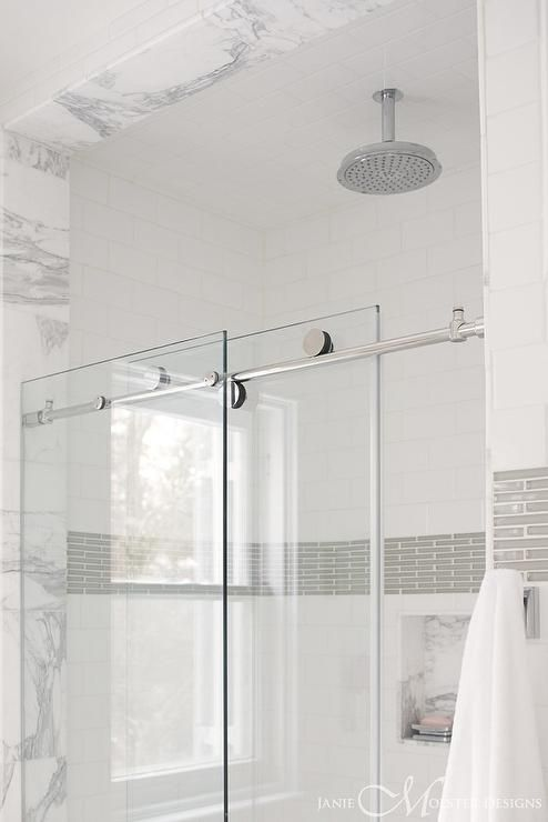 Glass doors on rail slides open to reveal a walk in shower filled with white subway tiles accented with a border of gray tiles alongside a marble tiled shower niche.