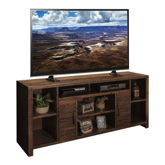 Display your flat screen in charming style with this American-made TV stand, the perfect piece for rounding out your space in rustic style. The whiskey finish and wood grain detailing lend a touch of lodge-worthy style to this design, while the 7 open shelves and 2 cabinets give it essential storage space and functionality. Try setting this striking stand in your living room and top it with your television for the perfect vantage point to watch blockbuster movies and Sunday night football…