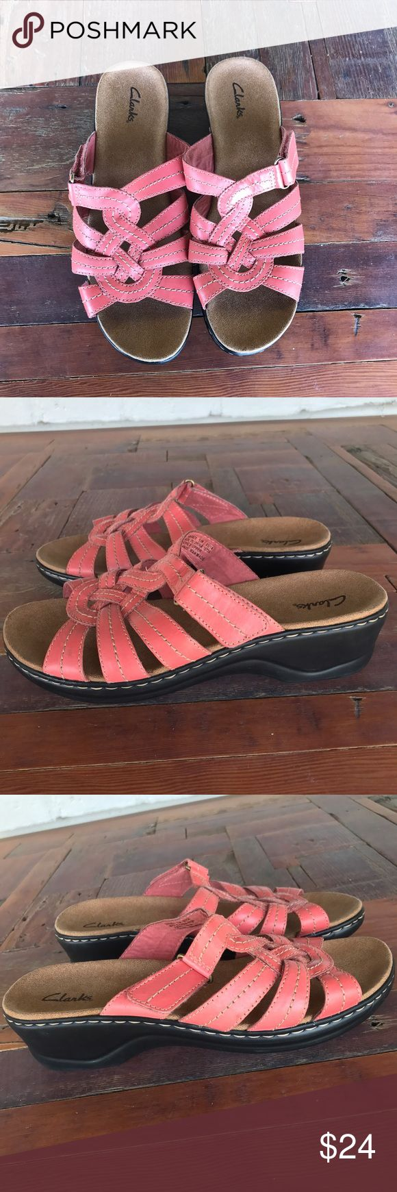 Clarks Lexi Dill Coral Leather Sandal Velcro Strap Clarks Lexi Dill Coral sandals. A beautiful coral pink leather sandal with tan footbed and black rubber sole. Velcro strap on side gives a personalized fit. There is a small, 2 inch lift wedge on these. Soft and comfortable footbed makes these perfect for vacation, travel, or everyday wear. Leather is woven and braided together. Excellent condition, no flaws or signs of wear. Sticker says Tige de Cuir. Bundle for a 20% discount. Clarks Shoes…