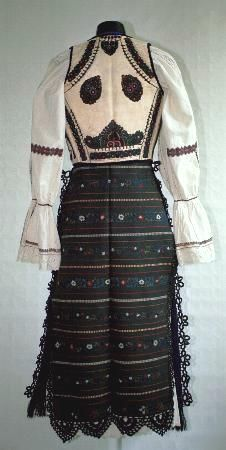 Romanian Women's costume, county of Sibiu, zone Rupea;  White linen underskirt (poale) with a row of embroidery on hem and edged with white crochet lace. Gathered front apron (Şorţ ) made of blue fabric and edged with black crochet lace on the side edges and a black silk frnge on the hem. Back apron (catrinţă) is a single width of black woven material with horizontal woven stripes in red and gold thread, with interleaved floral embroidered motifs in red and blue. edged with black crochet…