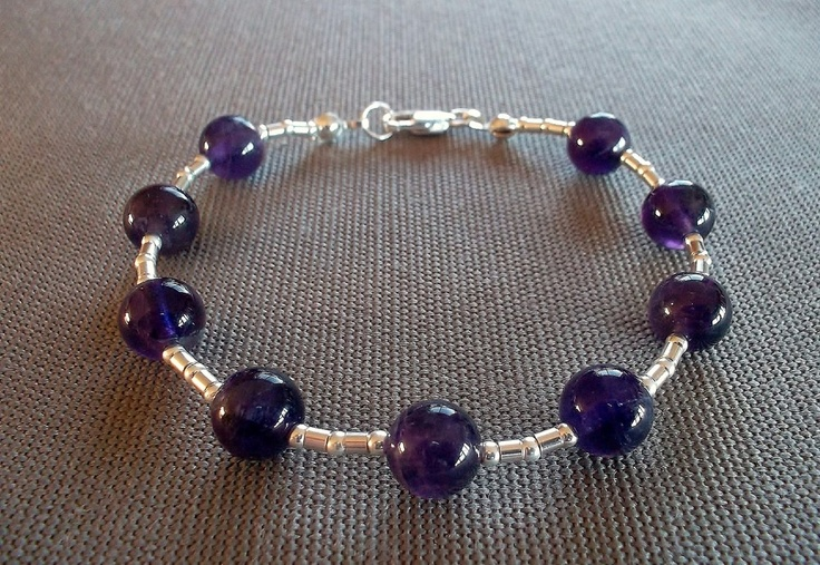 Handcrafted bracelet featuring 8mm round genuine amethyst beads and sterling silver beads and clasp. 8 inches in length.