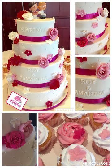 4-laags bruidstaart in wit met diamant patroon en suiker parels. Gedecoreerd met roosjes en sier bloemetjes in roze tinten.