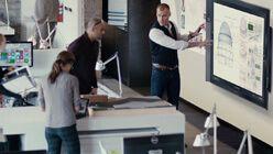 Un homme utilisant l'écran tactile du Microsoft Surface Hub et un homme et une femme au comptoir