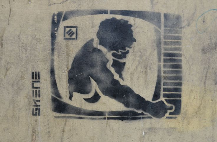 black stencil on grey concrete wall, man reaching out from inside a TV to turn the TV off, by Skene