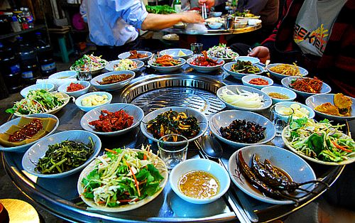 Table setting around a Korean BBQ grill. To meet standards, the many complimentary side dishes (Banchan 반찬, varies by location & restaurant) arrives before the main food!
