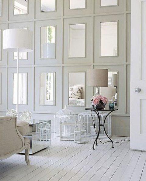 Повторяющиеся зеркала в больших белых рамах на стене делают потрепанное шикарное пространство немного более современным