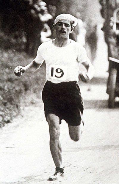 Italian Dorando Pietri holds a commanding lead in the 1908 Olympic marathon in London, well before falling victim to exhaustion with less that 400 meters remaining.  He was disqualified and American Johnny Hayes claimed the gold medal and  victory.