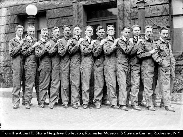 """""""Kodak Park overalls lead new style"""" Thirteen Kodak Park workers line up on the sidewalk in their matching coveralls in 1920.  .  Subject(s):Clothing & dress--New York (State)--Rochester.  Coveralls--New York (State)--Rochester."""