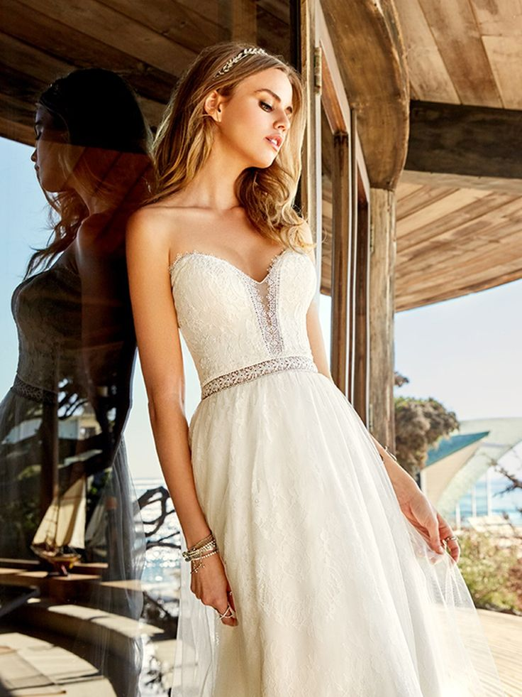 This strapless and sexy beach wedding dress from Simply Val Stefani is pure romance. The tulle/lace fabric is beautifully breezy. Perfect for a ceremony by the ocean. But the sweet style of Bay is also blended with Boho details, lovely for a garden or barn ceremony. The lacy sweetheart neckline features wispy eyelashes and an illusion inset with a Venise lace fabric trim; the vintage look of the needle lace softens the deep inset. A sheer lace inset around the waist complements a…
