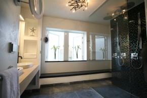 Attraente bagno con doccia.  Il bagno moderno ha un carattere molto invitante.  Facendo buon uso di colori e materiali naturali crea una calda atmosfera nella stanza da bagno.  L'illuminazione indiretta sotto il zitplateau sotto la tenda finestra sottolinea la sospensione del plateau e fornisce anche l'illuminazione di orientamento durante la notte.  MD design