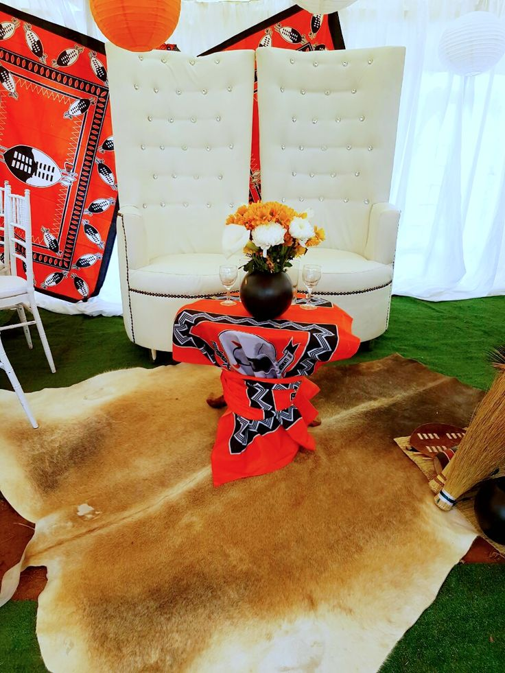Orange and black traditional Swazi wedding decor - bride and groom chairs - Shonga Events