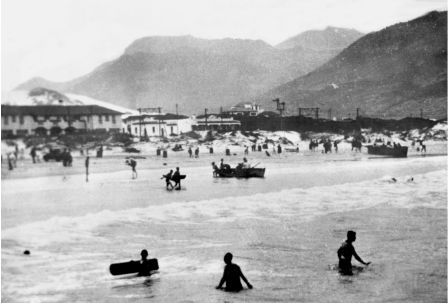 Fish Hoek Beach 1929 At the left the Windsor Hotel. The white building is the station with sand dunes behind it.