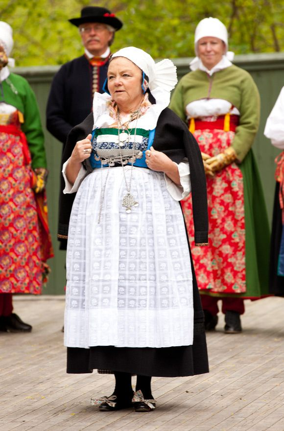 "SE Oxie kvinnodräkt. Skåne Photo-Laila-Duran. Scandinavian Folklore.  The wife is dressed for a festive occasion with a white head dress and apron. She is also wearing ""öronsvansar"" (ear tails) a fashionable detail that would keep the ears warm."