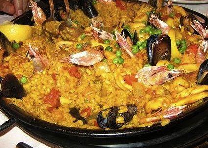 Ricetta per preparare la paella valenciana di pollo e pesce con zafferano, vongole, cozze, aragoste, pollo, pancetta e prosciutto