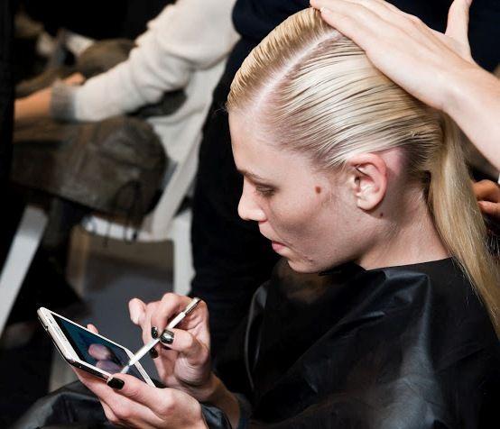 Très concentrée sur son #GalaxyNote, Aline Weber se fait coiffer en attendant de s'élancer sur le podium de la #Fashion Week ! #Samsung #Galaxy #Style